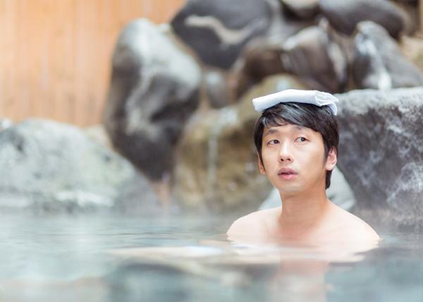 温泉でぼんやりする男性
