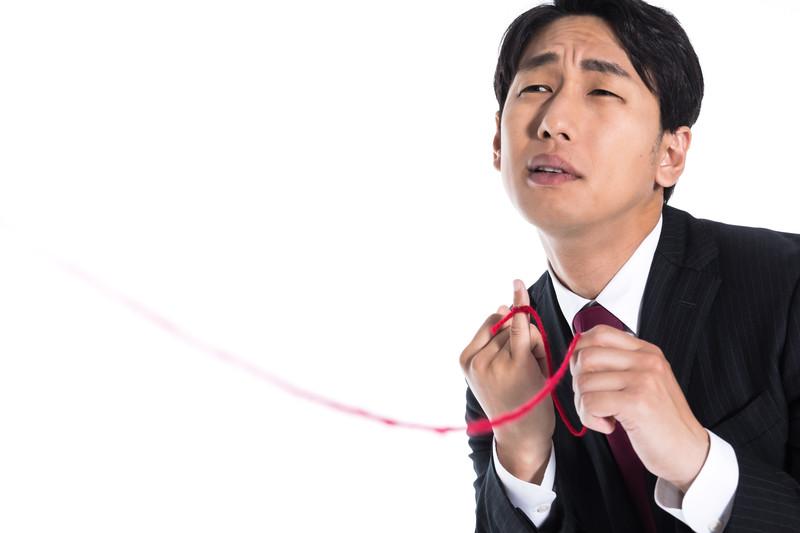 赤い糸に縋る男性